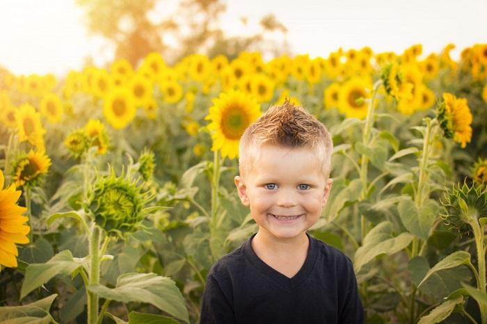 Copil vesel in lan de floarea soarelui